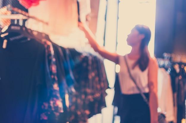 Помутнение фон женщины, глядя на одежду