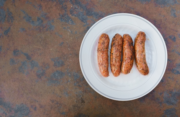 Blurred background of party in garden and brown sausage and kitchen desk pork sausages on fire