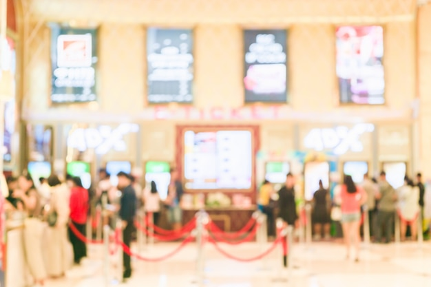 Blurred background of people buying ticket from movie e-ticket machine