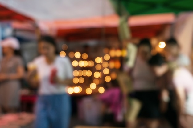 Blurred background of people shopping at night market festival for background usage.