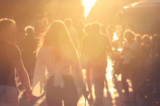 Blurred background people walking on street with sun flare