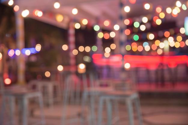 背景をぼかした写真。テーブルと椅子のあるレストランは、ボケの光で背景をぼかします。夜の時間