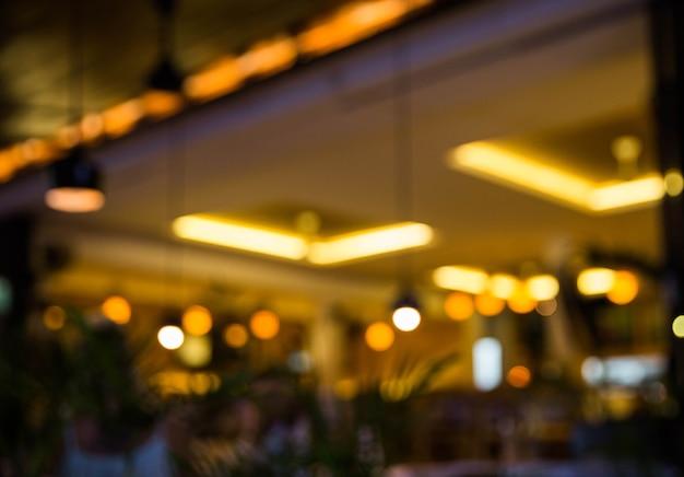 背景をぼかした写真。テーブルと椅子のあるレストランは、ボケの光で背景をぼかします。