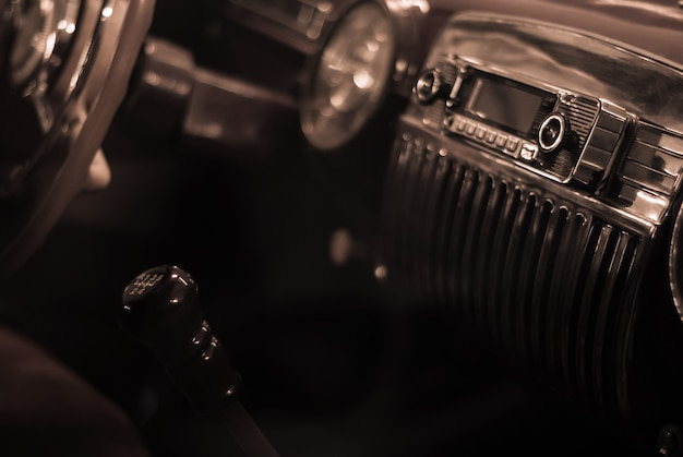 Blurred background stylized as old monochrome photo- a fragment of the interior of a vintage car, focus on the handle of the radio