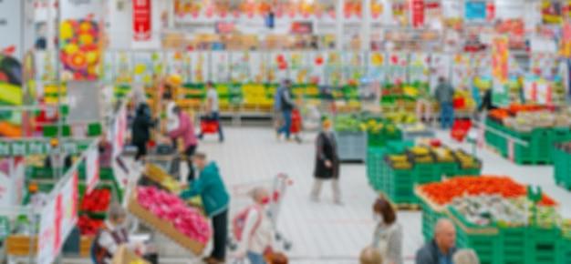 배경을 흐리게. 슈퍼마켓 인테리어. 슈퍼마켓에서 야채와 과일 판매. 매장 내 고객.