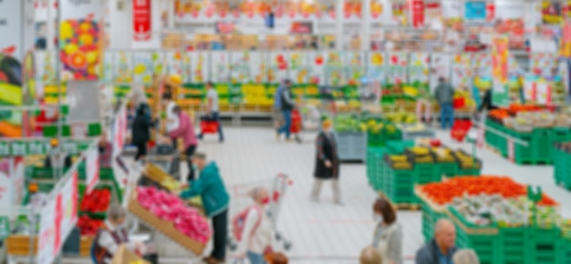 Blurred background. supermarket interior. selling vegetables and fruits in supermarket. customers in store.