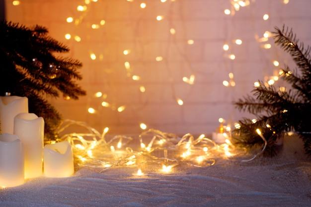 新年とクリスマスをテーマにしたコラージュのためのモミの枝のものと光の輝く花輪でぼやけた背景。