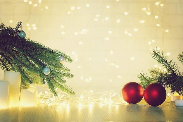 クリスマスと新年のコラージュのための赤いボールとモミの枝の花輪とぼやけた背景。