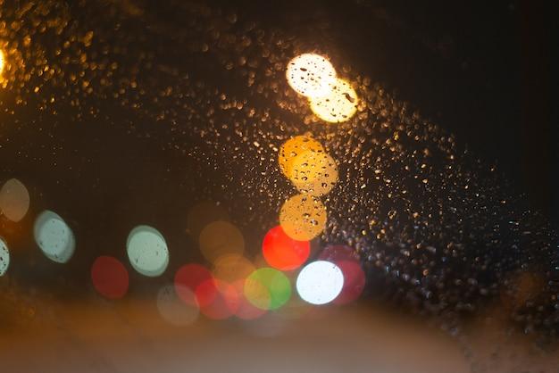 雨滴とライトでぼやけた背景