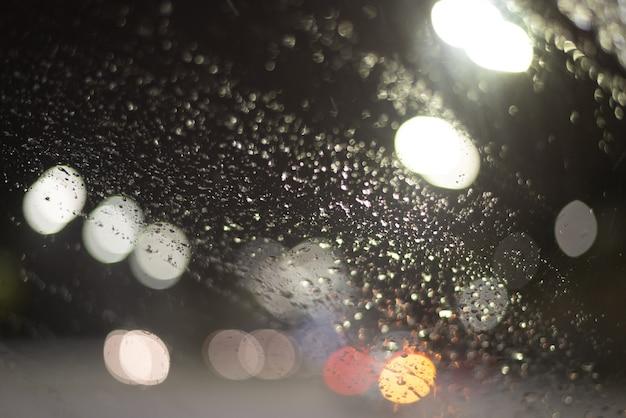 Размытый фон с каплями дождя и огнями.