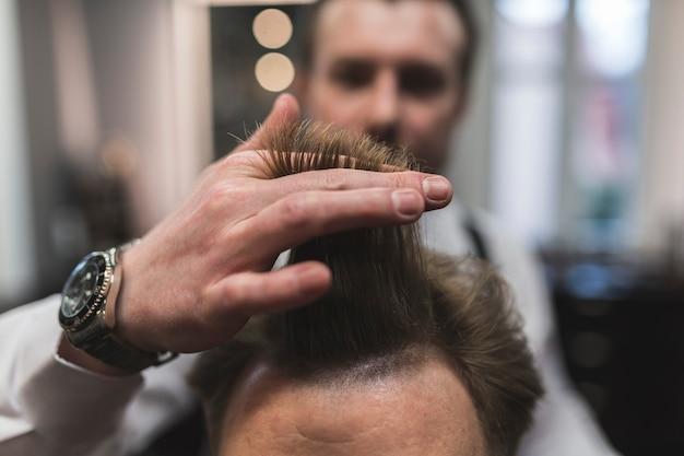 Blurred barber preparing to cut hair of man