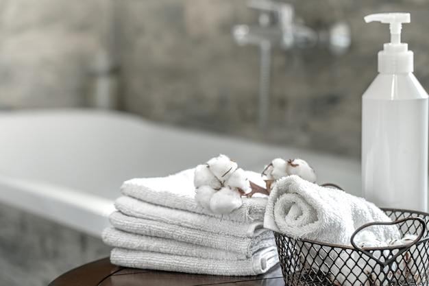 ぼやけたバスルームのインテリアと清潔な折り畳まれたタオルのセットはスペースをコピーします。衛生と健康の概念。