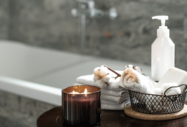 Blurred bathroom interior, cozy candle and set of clean folded towels.