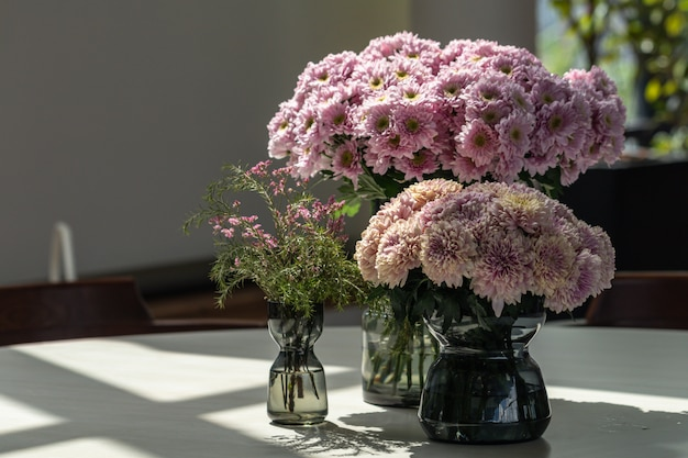 Blurred beautiful pink chrysanthemum flowers bouquet in glass vase on the table.