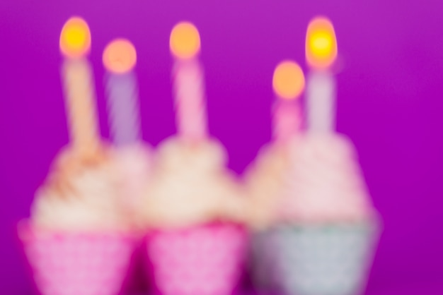 Blurred birthday cupcakes with lit candles