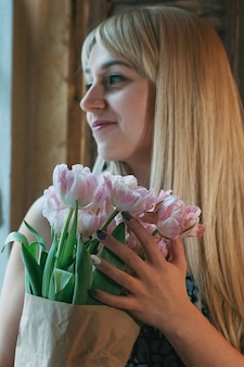 Blurred blonde woman with a bouquet of flowers by the window