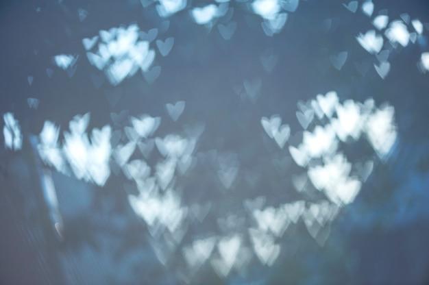 青い背景の上のハートのぼやけたボケ味抽象的な背景