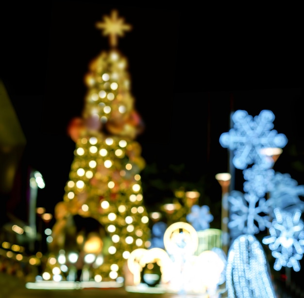 Blurred and bokeh view of christmas tree and decorate led lighting front of shopping mall on christmas night in urban city.