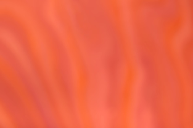 波状の巻き毛のパターンでぼやけた明るいオレンジと赤の背景。ぼけとボケ味のデフォーカスアート抽象的な生姜グラデーションの背景。シルクテキスタイル。