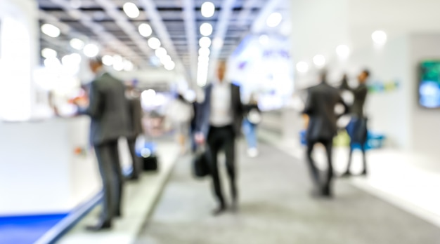 Blurred businesspeople at generic trade show expo stand