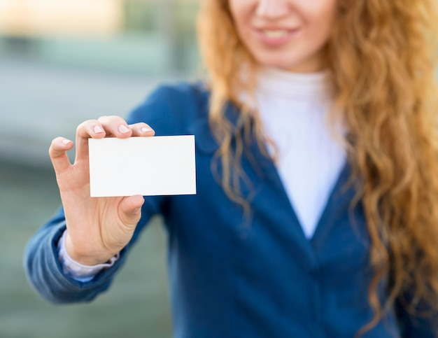 Blurred businesswoman holding a business card