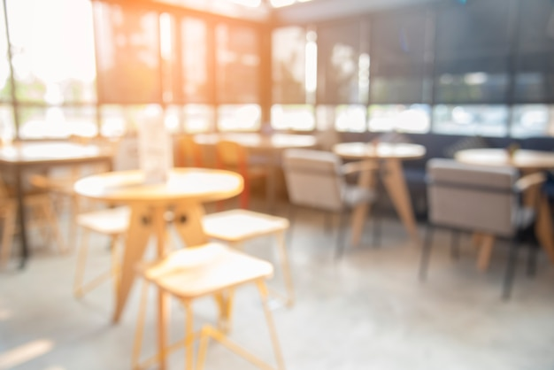 Blurred cafe coffee shop with sun light. abstract of modern table design in restaurant.