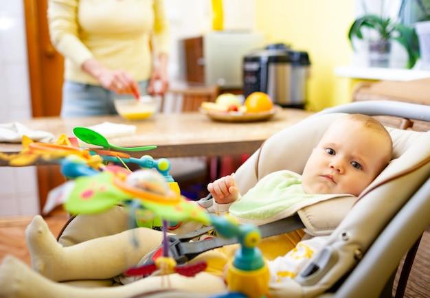 ぼやけた魅力的な笑顔のお母さんはテーブルに座って、おもちゃで彼女のベビーシートで遊んでいる彼女の小さな陽気な新生児の女の子を喜んでいます。幸せな母性の概念