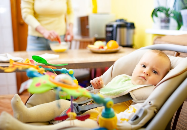 Blurred charming smiling mom sits at the table and rejoices at her little cheerful newborn baby girl playing in her baby seat with toys. happy motherhood concept