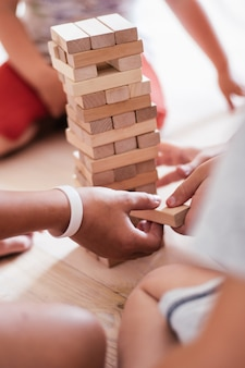 흐릿한 어린이 손은 나무 블록으로 만든 탑으로 게임을 합니다. 수직의