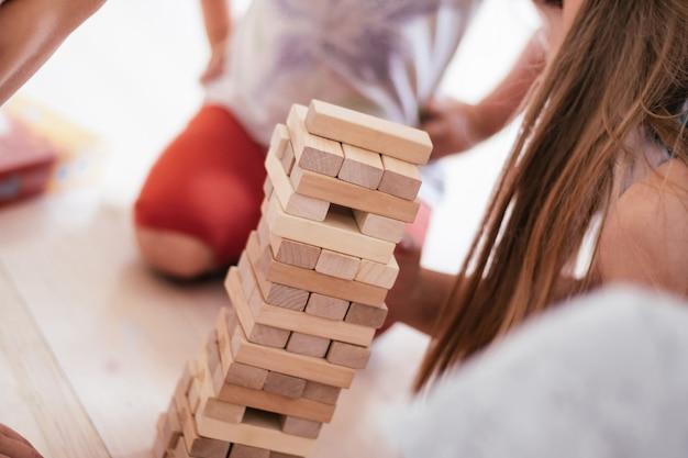 흐릿한 어린이 손은 나무 블록으로 만든 탑으로 게임을 합니다.