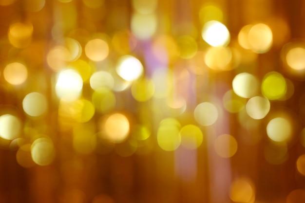흐릿한 크리스마스 조명은 황금빛 반짝이의 밝은 반짝임을 보케합니다.