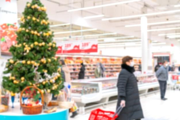 흐리게 크리스마스 슈퍼마켓 인테리어. 식료품 점의 쇼핑객.