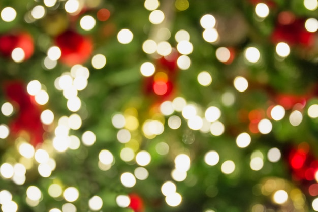 Blurred christmas tree with golden garland and red balls. abstract background. xmas.
