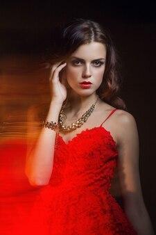 Размытый цветной художественный портрет девушки на темном фоне. женщина моды с красивым макияжем и легким летним платьем. чувственный нежный образ девушки в движении. студийный портрет