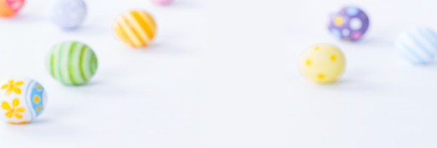 ハッピーイースターの日のコピースペースと白い背景のぼやけたカラフルな卵。