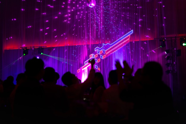 Blurred concept at concert party with audience and colourful led lighting.