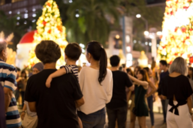 Blurred conceptual holiday event party outdoor with blurred people and christmas tree