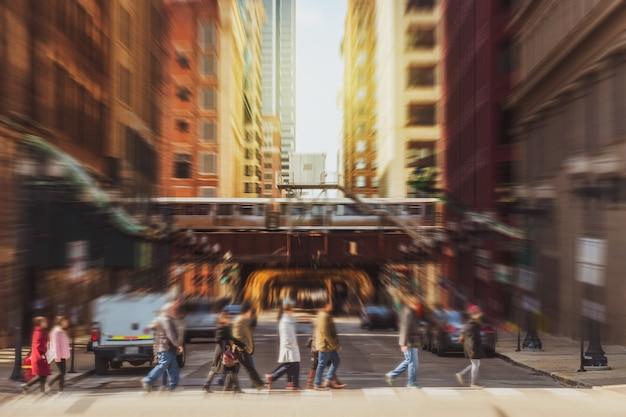 Размытая толпа на улице чикаго с перекрестком транспортных дорог в час пик среди современных зданий