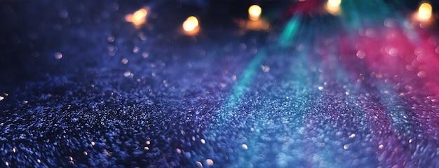 Размытый темный абстрактный фон с блестящими огнями боке ультрафиолетовые сверкающие огни