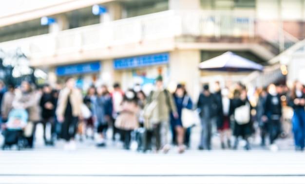 通りを歩く人の多重の抽象的な背景をぼかした写真