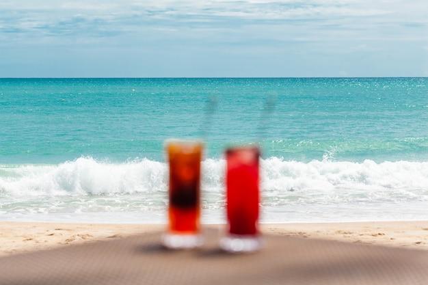 Размытые расфокусированные экзотические коктейли на столе у моря в концепции рая