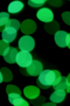 Blurred, defocused, out of focus, bokeh vibrant green light on black for abstract background