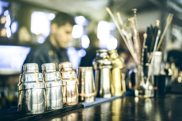 Blurred defocused view of barman preparing drinks at speakeasy cocktail bar on happy hour