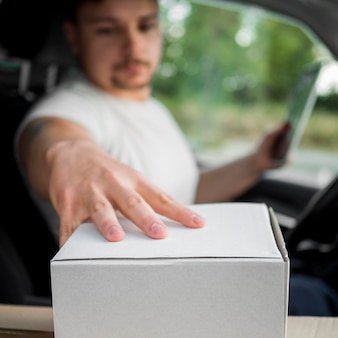 Blurred delivery man in car touching box