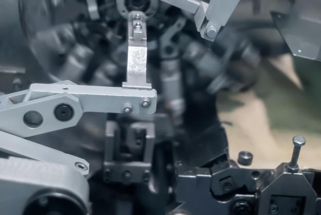 ぼやけた薄暗い産業の背景、動いているお菓子を梱包するための機械の断片