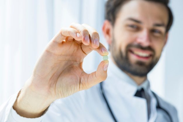 Blurred doctor showing pill