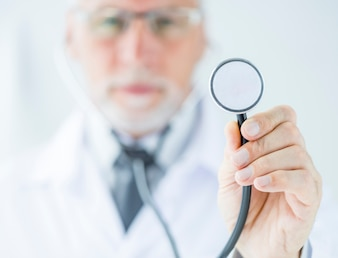 Blurred doctor showing stethoscope