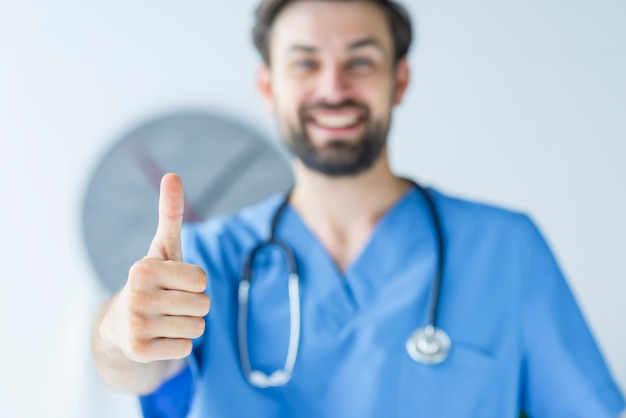 Blurred doctor showing thumb-up gesture