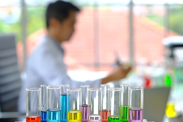 Blurred doctor sit analyzing in laboratory room have color testing glass straw foreground.