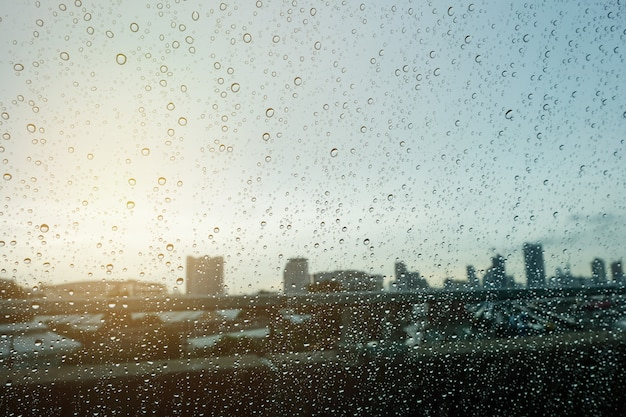 Blurred droplet in car windows and sun light over morning city
